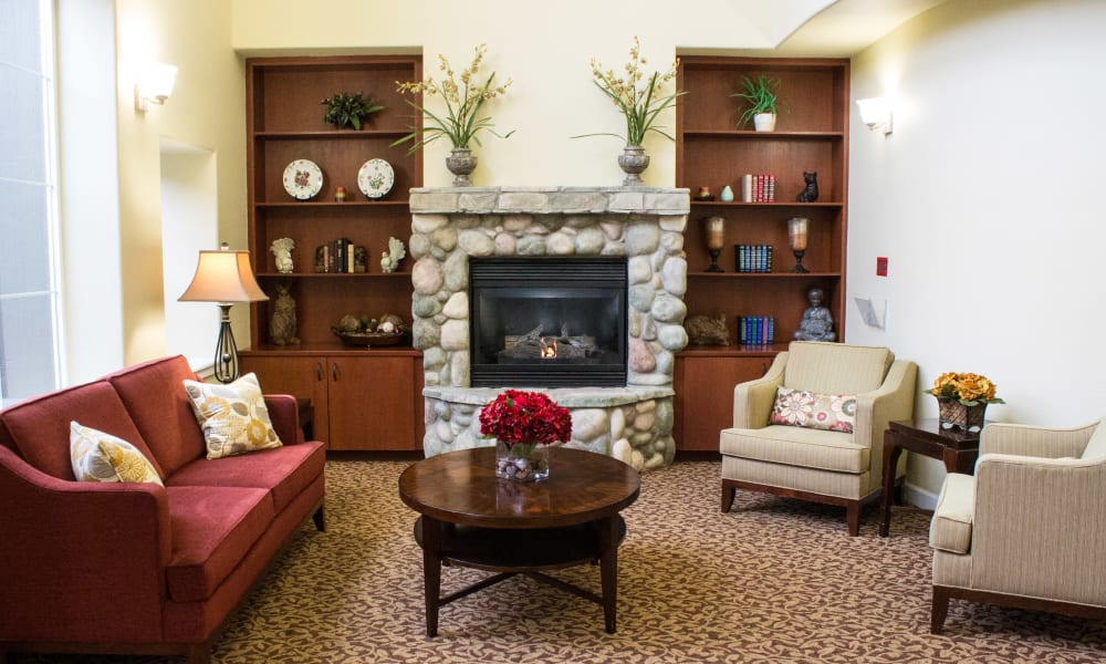 Reading corner with seating and a fireplace at Evergreen Memory Care in Eugene, Oregon