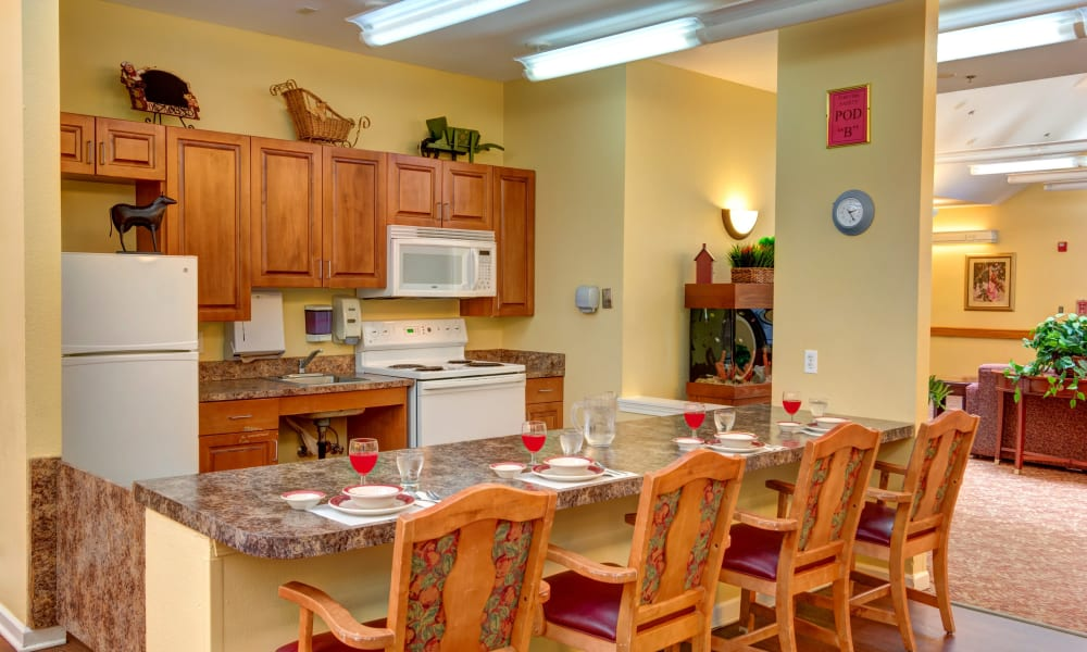 Dining seating in front of the kitchen at Rosewood Memory Care in Hillsboro, Oregon