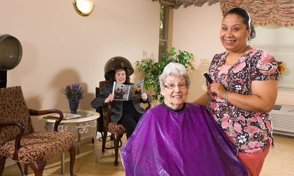 Resident getting her hair cut at The Manor at Market Square in Reading, Pennsylvania