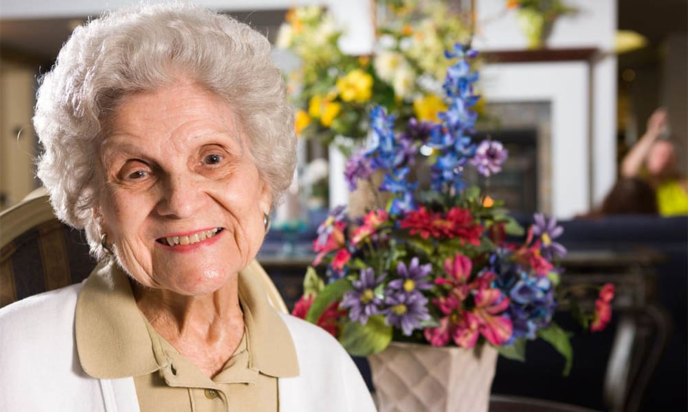 happy Resident posing for a photo next to some flowers at The Manor at Market Square in Reading, Pennsylvania