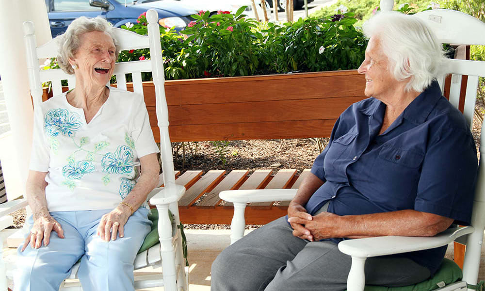 Two residents laughing while relaxing on the patio at Heritage Green in Lynchburg, Virginia