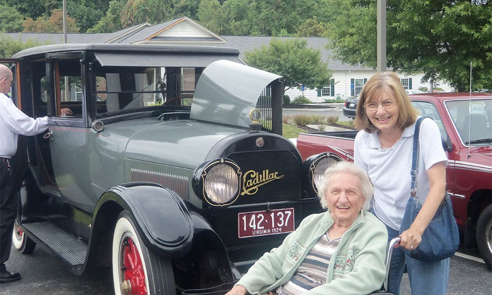 Two residents in front of a classic car at Heritage Green in Lynchburg, Virginia
