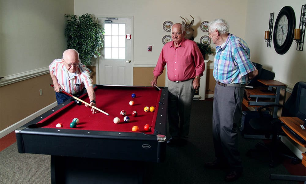 Three elderly residents playing billiards at Heritage Green in Lynchburg, Virginia