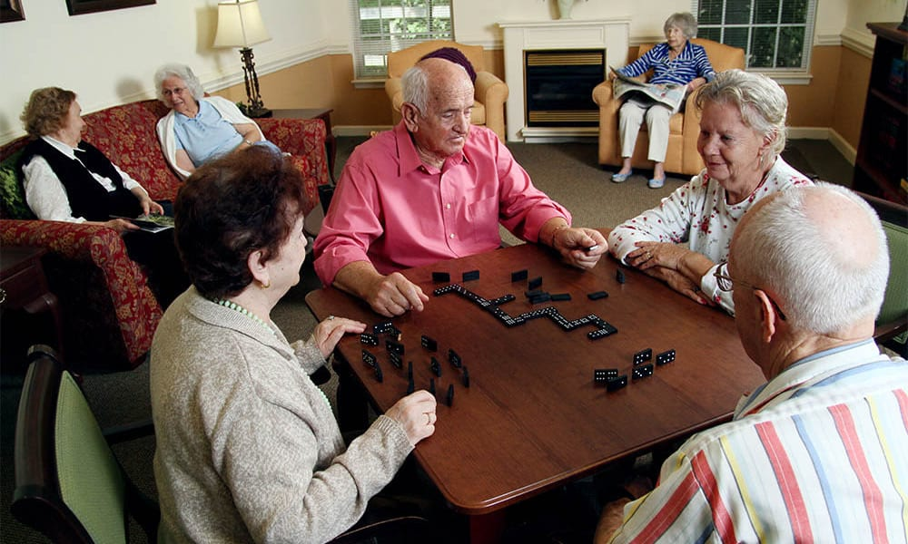 Four residents playing a game of dominoes at Heritage Green in Lynchburg, Virginia