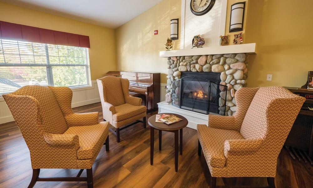 A set of comfortable chairs in front of a fireplace at Lakeland Senior Living in Eagle Point, Oregon