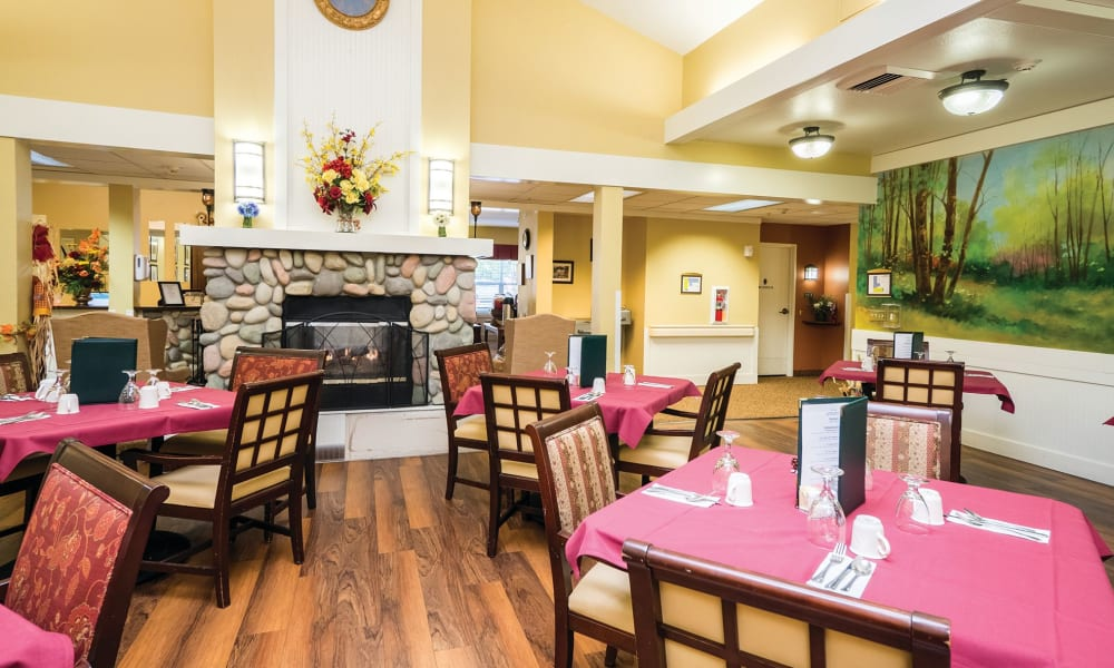 Dining tables arranged in front of a fireplace at Lakeland Senior Living in Eagle Point, Oregon