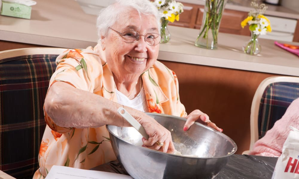 Resident making something in a large bowl at Senior Commons at Powder Mill in York, Pennsylvania