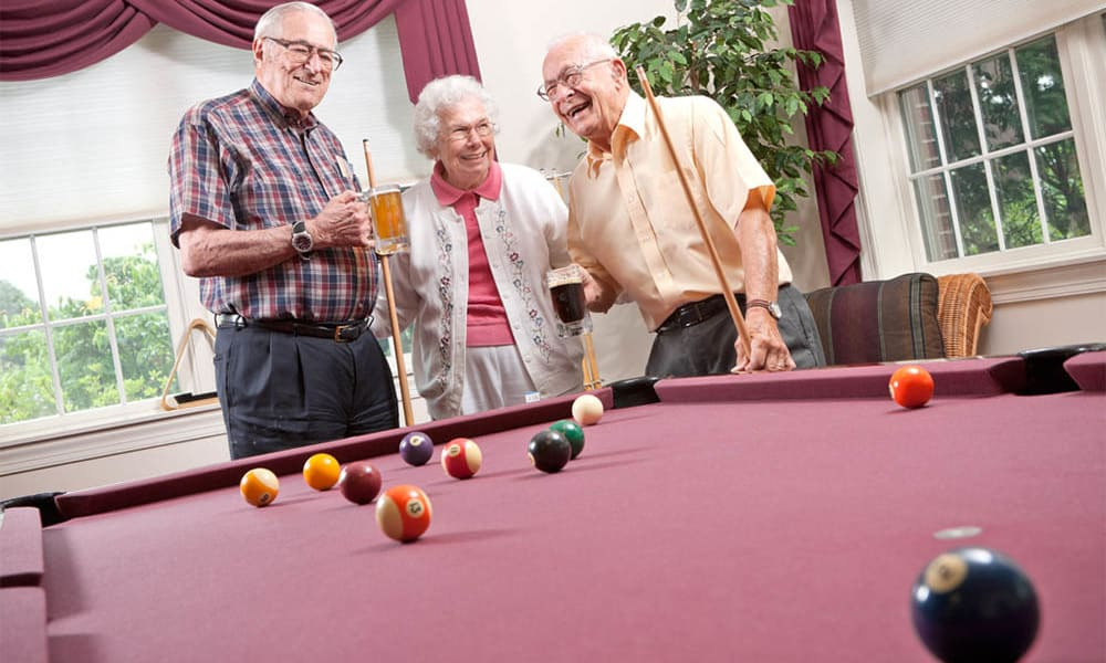 3 Residents playing billiards at Senior Commons at Powder Mill in York, Pennsylvania
