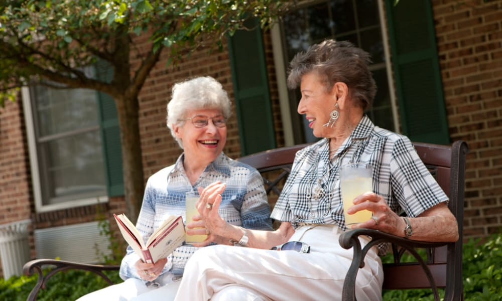 Two residents sitting outside sharing drinks Senior Commons at Powder Mill in York, Pennsylvania