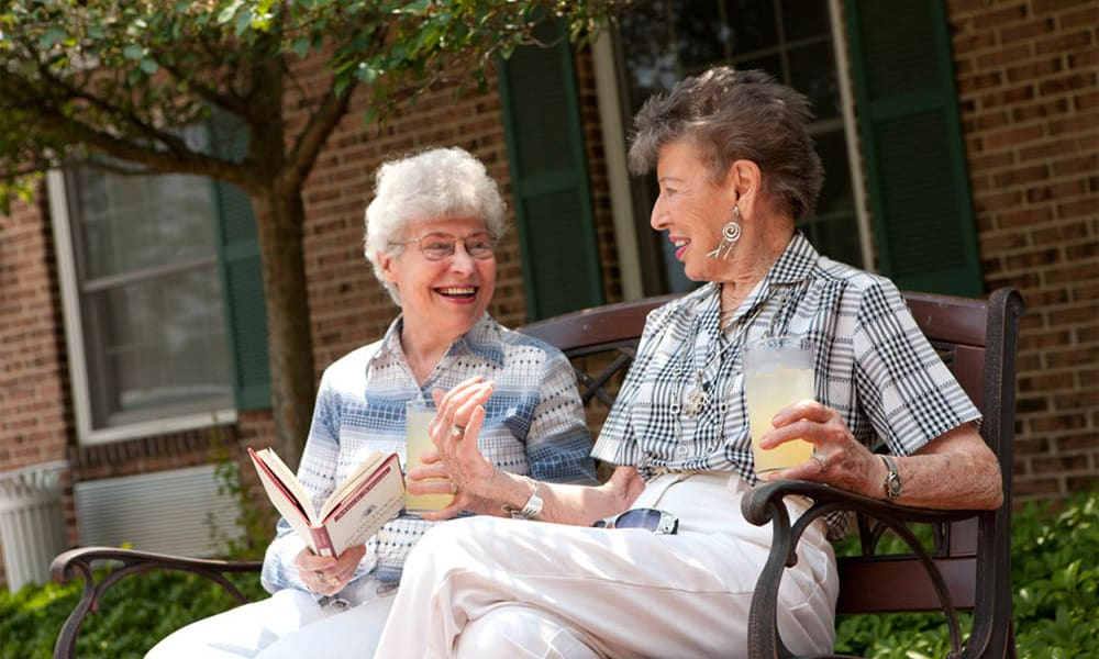 Two women reading on a bench at Senior Commons at Powder Mill in York, Pennsylvania