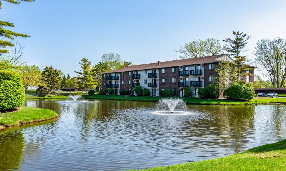 Pond with fountains at Oldebrook Apartments in Wyoming, Michigan