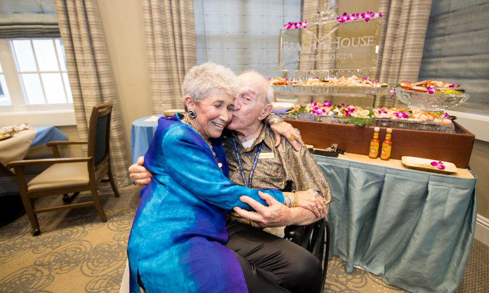 Senior man and woman hugging at Beach House Assisted Living & Memory Care Naples in Naples, Florida