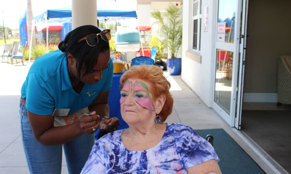Staff member and resident face painting at Beach House Assisted Living & Memory Care Naples in Naples, Florida