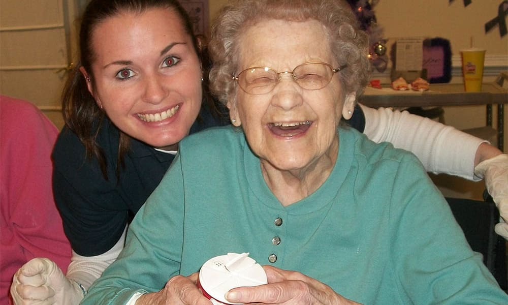 Resident and care worker laughing at Heritage Green Assisted Living in Mechanicsville, Virginia