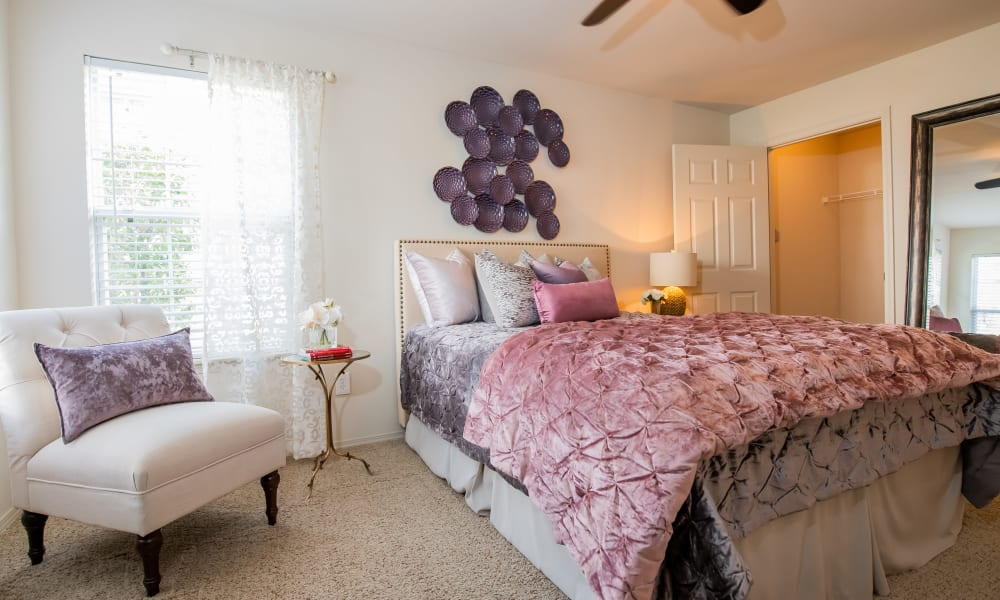 An apartment bedroom with pink bed covers at Colonies at Hillside in Amarillo, Texas