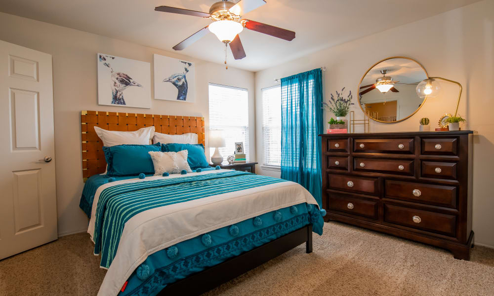 An apartment bedroom with blue bed covers at Colonies at Hillside in Amarillo, Texas