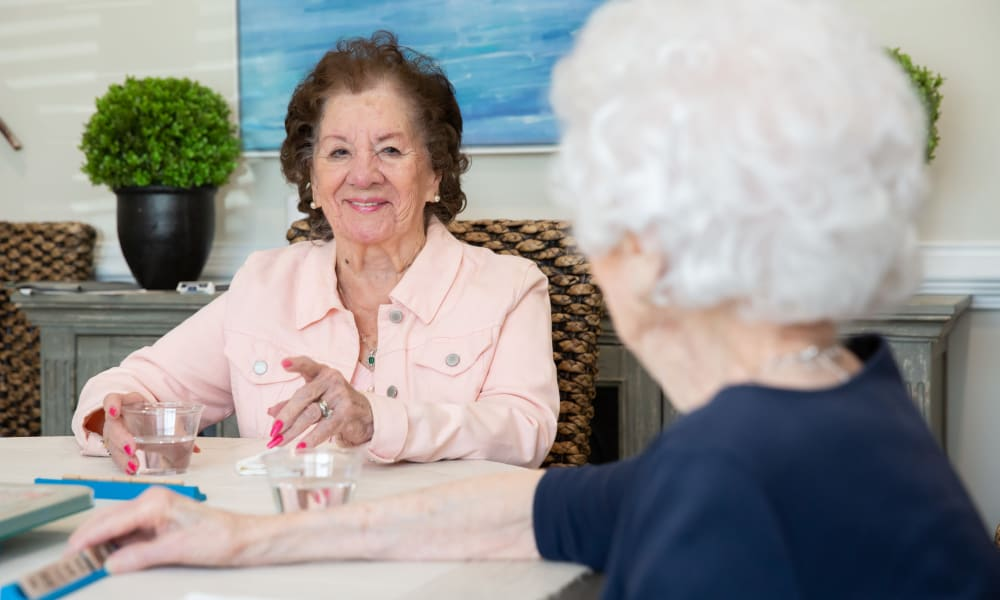 Two residents drinking water and talking at The Mansions at Sandy Springs Assisted Living and Memory Care in Peachtree Corners, Georgia