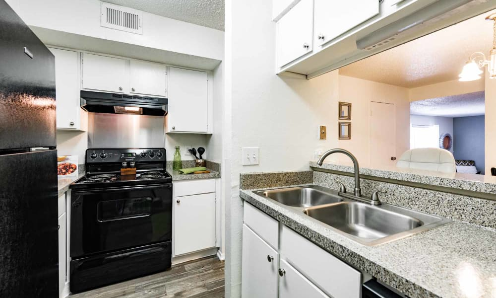Apartment kitchen with sink, refrigerator, and stove at The Summit at Landry Way in Fort Worth, TX