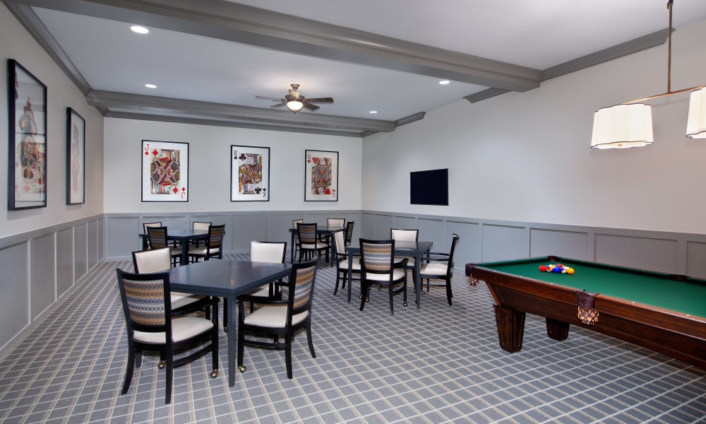Billiards table and seating in the game room at Keystone Place at Naples Preserve in Naples, Florida