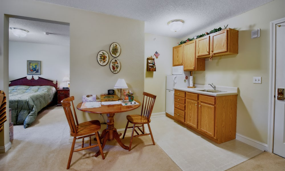 A dining room and kitchen at The Keystones of Cedar Rapids in Cedar Rapids, Iowa