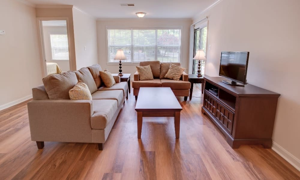 Living room with large windows at Abbotts Run Apartments in Alexandria, Virginia.