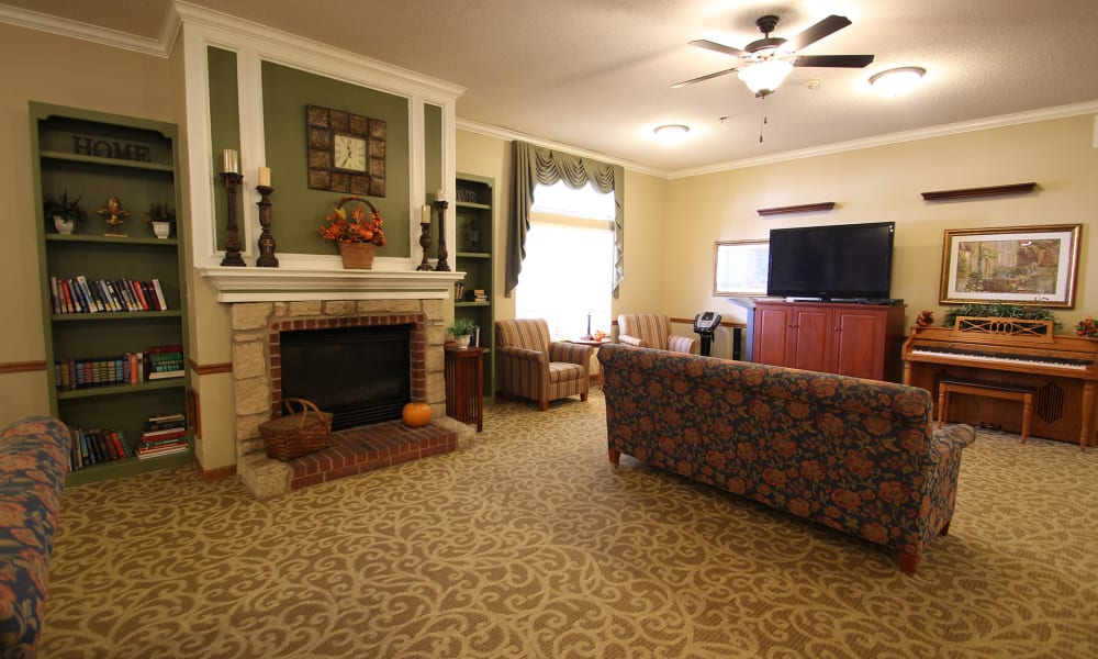 Lounge with a fireplace, tv, and a piano at Chandler Place Independent Living in Rock Hill, South Carolina