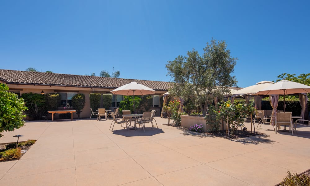 Outdoor patio with tables, chairs, and umbrellas at Vista Gardens in Vista, California