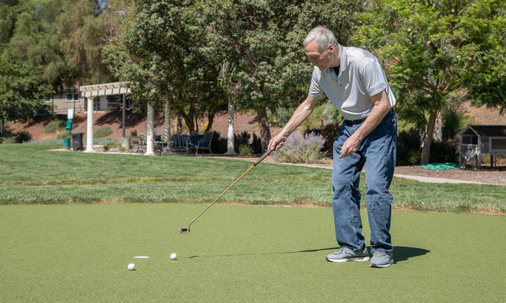 Senior man putting on putting green at Vista Gardens in Vista, California