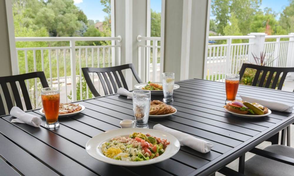 Outdoor dining table set on the porch at Anthology of Rochester Hills in Rochester Hills, Michigan