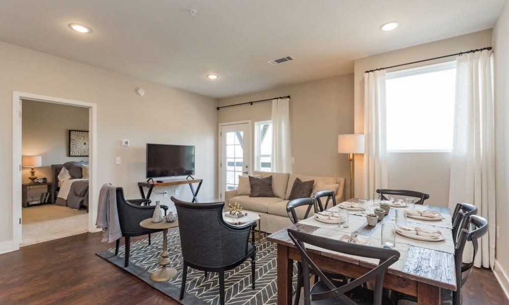 Dining room table and living room in a model home at Rivertop Apartments in Nashville, Tennessee