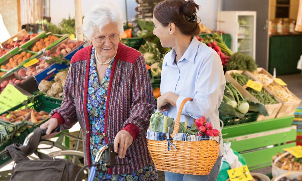 Resident shopping for groceries with a caretaker near The Phoenix at Savannah in Savannah, Georgia