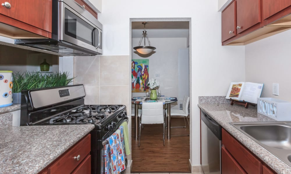 An apartment kitchen leading to the dining room at The Vibe at Clear Lake in Webster, Texas