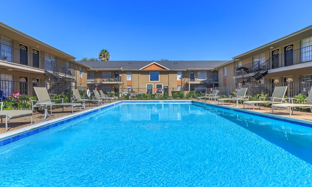 The community pool between apartment buildings at The Vibe at Clear Lake in Webster, Texas