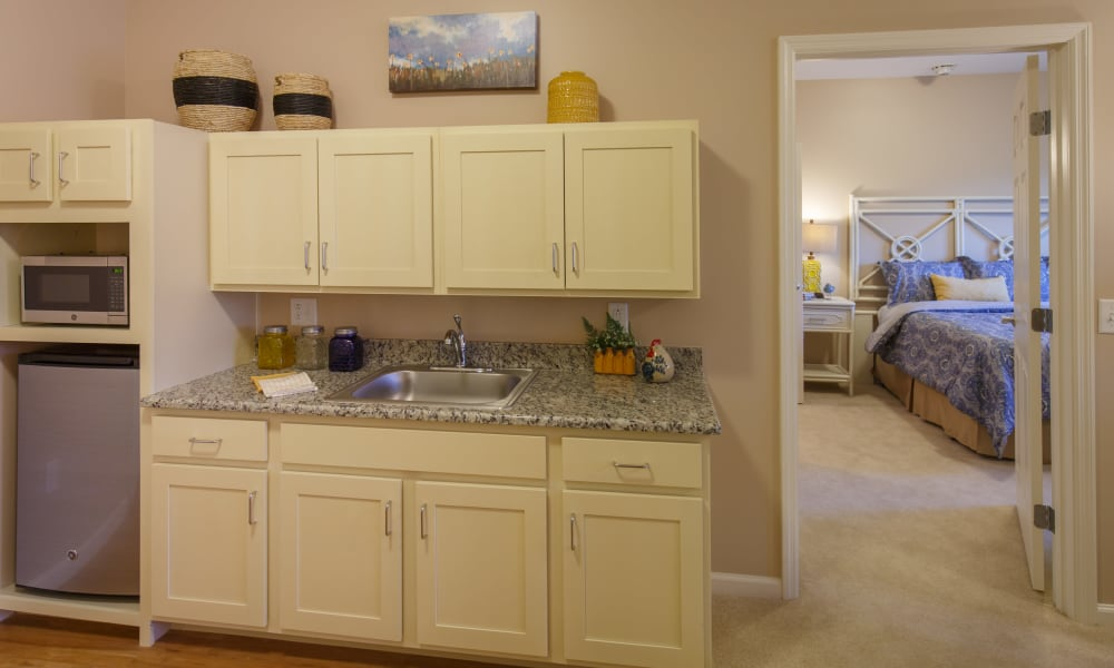 Kitchenette and resident bedroom at Keystone Place at Terra Bella in Land O' Lakes, Florida.