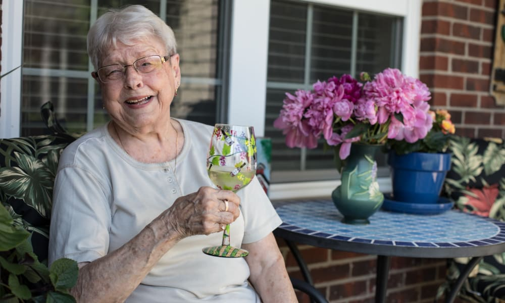 A resident enjoying a beverage outside at The Keystones of Cedar Rapids in Cedar Rapids, Iowa.