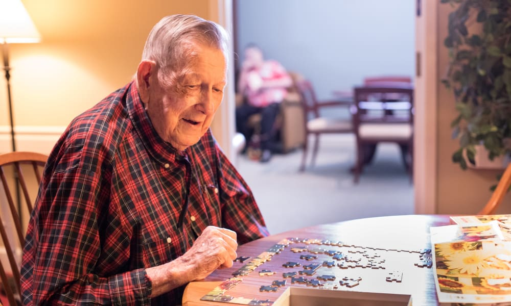 A resident putting together a puzzle at The Keystones of Cedar Rapids in Cedar Rapids, Iowa