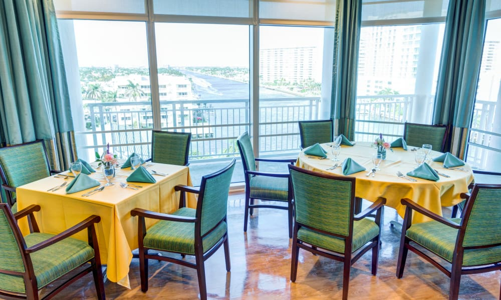 A square and round dining table seating 4 people each at The Meridian at Waterways in Fort Lauderdale, Florida