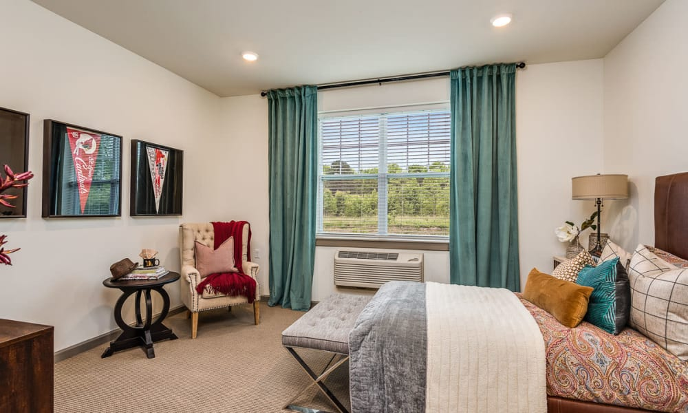 Resident model bedroom with large windows at Anthology of Wildwood in Wildwood, Missouri