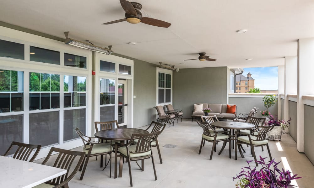 Covered patio with seating and ceiling fans at Anthology of Wildwood in Wildwood, Missouri.