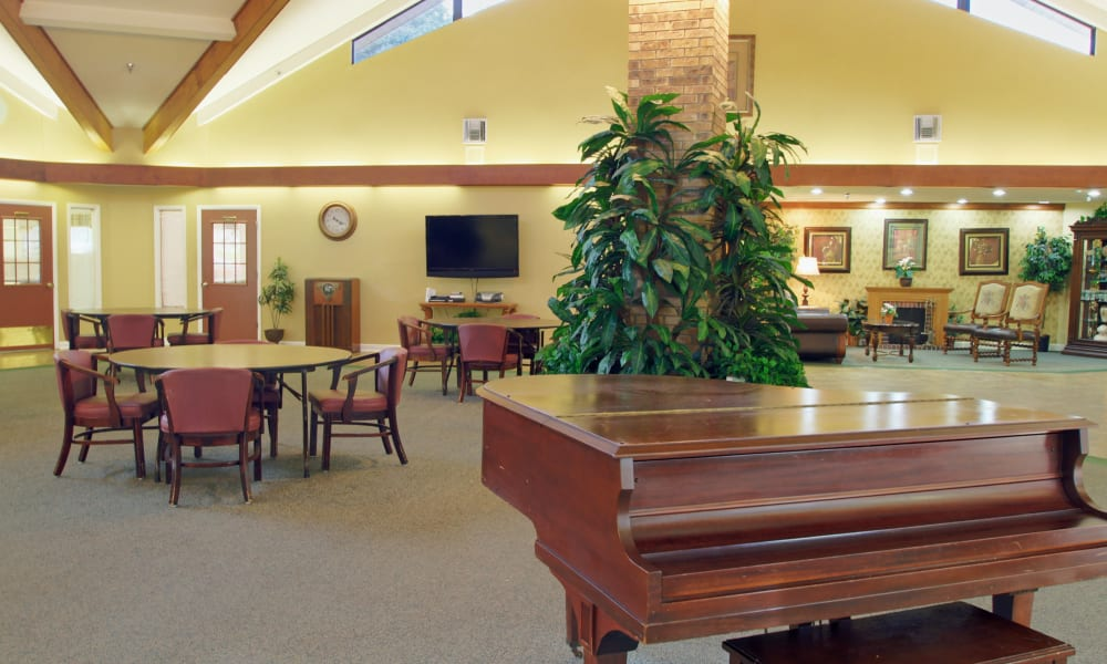 A community area with a piano at Forest Oaks of Spring Hill in Spring Hill, Florida