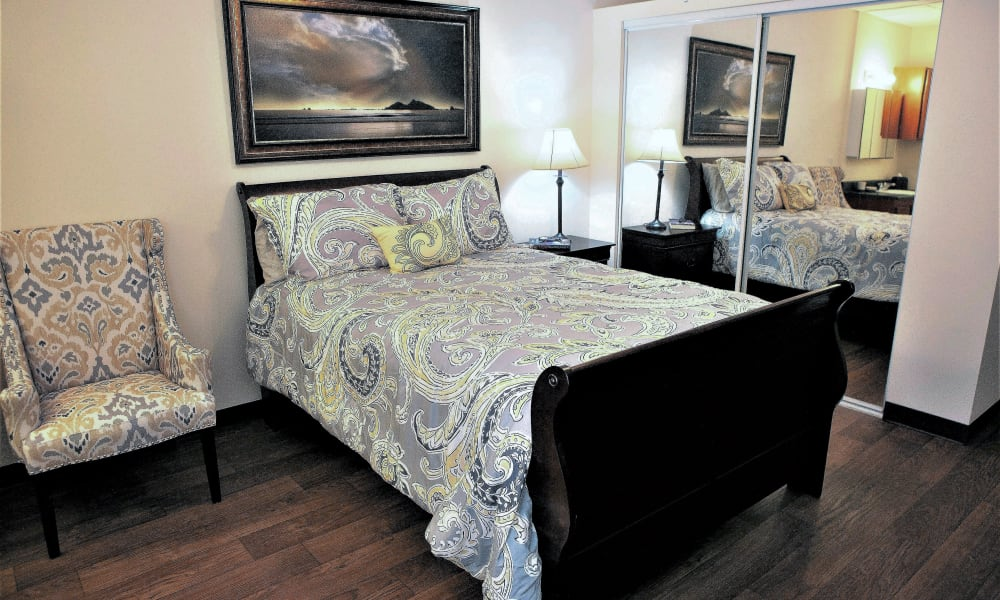 A spacious bedroom with a mirrored closet door at The Grande in Brooksville, Florida