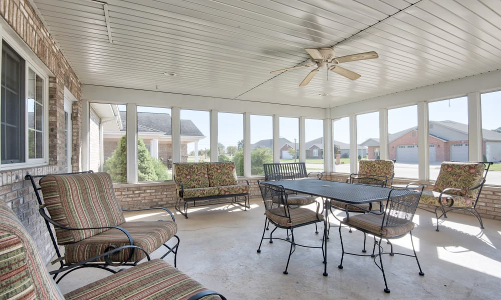 Covered outdoor patio with padded seating at The Villas at St. James in Breese, Illinois