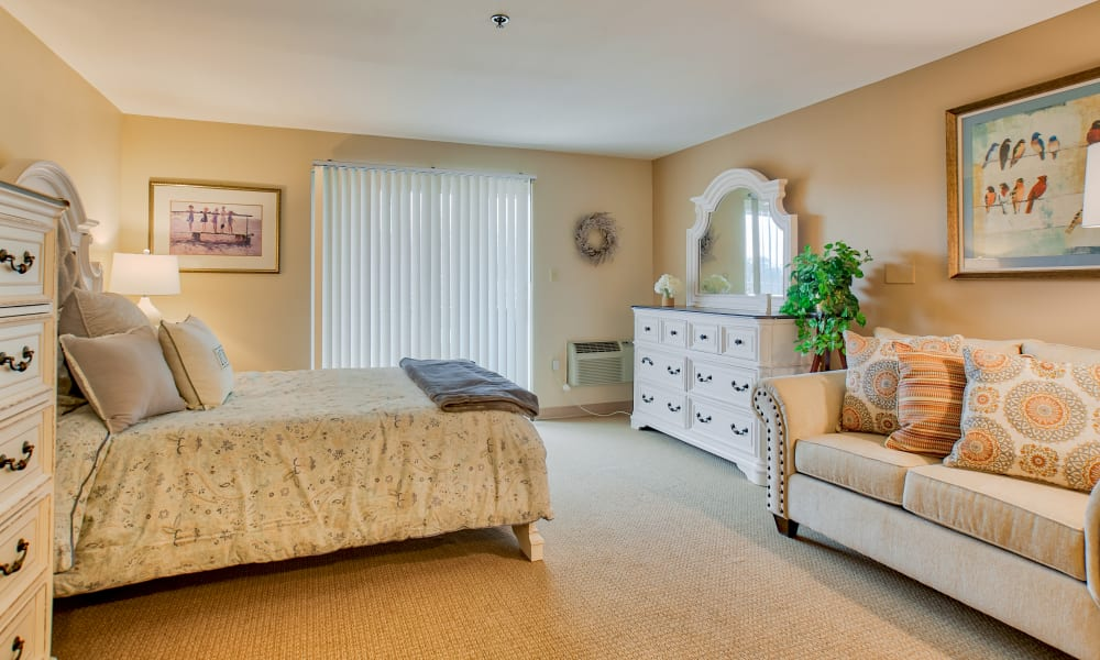 A spacious bedroom with a bed, two dressers and a couch at Chapel Hill in Cumberland, Rhode Island