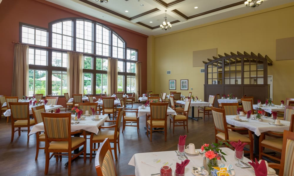 The dining hall with a large window at The Reserve at East Longmeadow in East Longmeadow, Massachusetts