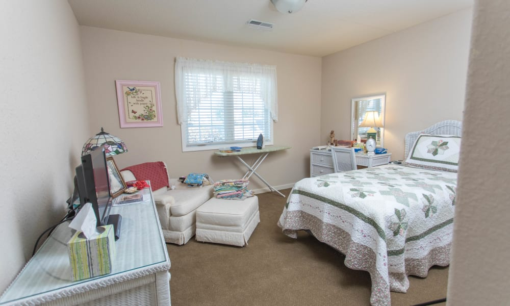 Single person bedroom with a tv and lots of furniture at Villas of Holly Brook Shelbyville in Shelbyville, Illinois