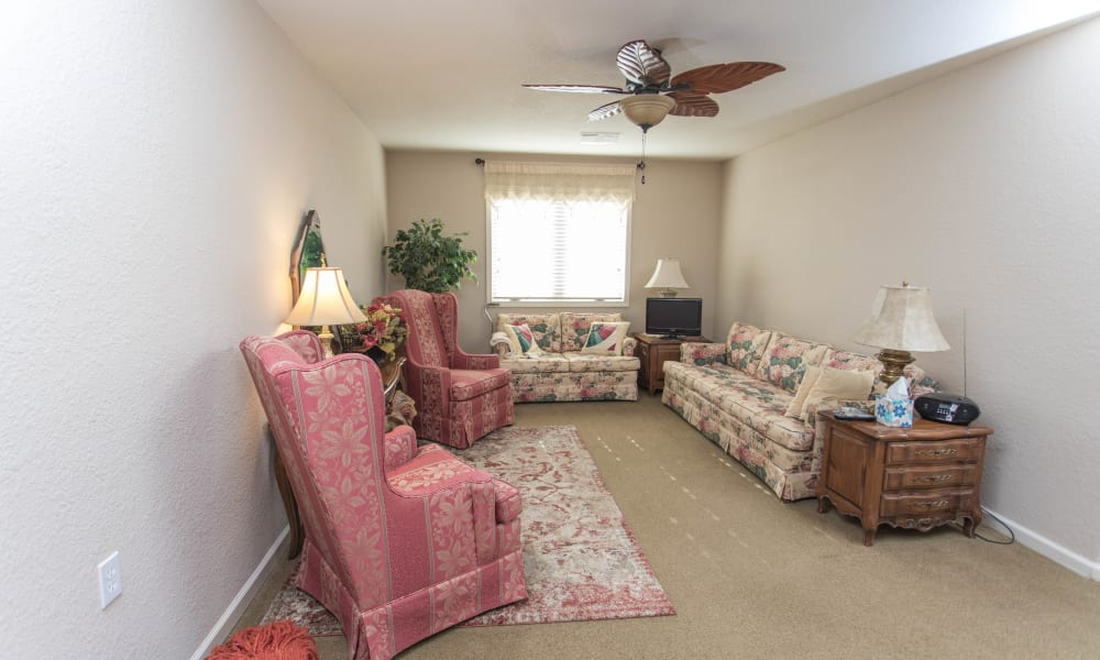 Inset senior apartment living room with 2 chairs and 2 couches at Villas of Holly Brook Shelbyville in Shelbyville, Illinois