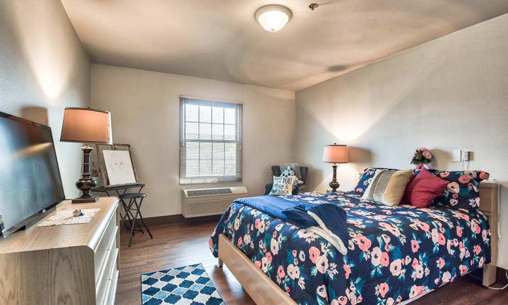 Studio senior apartment with a bed, tv, and seating at Oak Pointe of Warrenton in Warrenton, Missouri