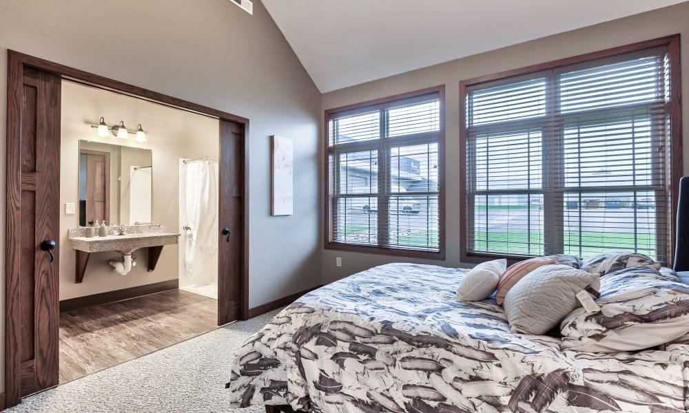 A bedroom with large windows at The Landings of Kaukauna in Kaukauna, Wisconsin