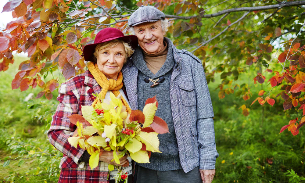 A happy couple collecting leaves near Honeysuckle Senior Living in Hayden, Idaho