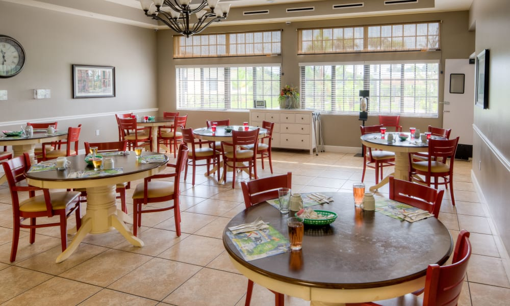 Open dining hall with large windows at Inspired Living in Bradenton, Florida